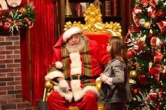 Χαριτωμένο μικρό κορίτσι που μιλά σε Άγιο Βασίλη στη διεθνή περιοχή Drive στοκ φωτογραφία