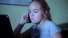 Χαριτωμένο μικρό κορίτσι που μιλά στην κινητή συνεδρίαση στον υπολογιστή Εξάρτηση στις συσκευές φιλμ μικρού μήκους