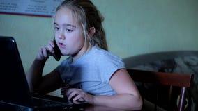 Χαριτωμένο μικρό κορίτσι που μιλά στην κινητή συνεδρίαση στον υπολογιστή Εξάρτηση στις συσκευές απόθεμα βίντεο