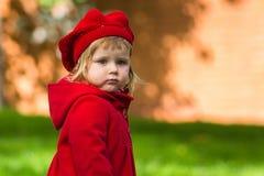 Χαριτωμένο μικρό κορίτσι που ντύνει στο κόκκινο παλτό στοκ φωτογραφία με δικαίωμα ελεύθερης χρήσης
