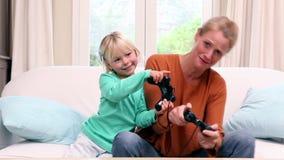 Χαριτωμένο μικρό κορίτσι που παίζει τα τηλεοπτικά παιχνίδια με τη μητέρα της απόθεμα βίντεο