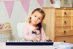 Χαριτωμένο μικρό κορίτσι που παίζει το ψηφιακό πιάνο ή τη σύνθεση ευτυχής διάθεση στοκ εικόνα με δικαίωμα ελεύθερης χρήσης
