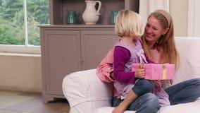 Χαριτωμένο μικρό κορίτσι που παίρνει ένα παρόν από τη μητέρα της φιλμ μικρού μήκους