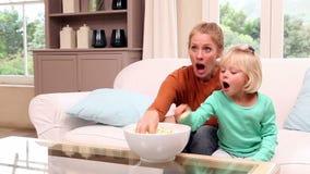 Χαριτωμένο μικρό κορίτσι που προσέχει τη TV με τη μητέρα της απόθεμα βίντεο