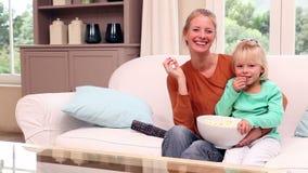 Χαριτωμένο μικρό κορίτσι που προσέχει τη TV με τη μητέρα της φιλμ μικρού μήκους