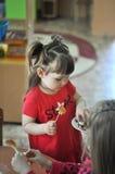 Χαριτωμένο μικρό κορίτσι που τρώει τις καραμέλες στον παιδικό σταθμό, σχολείο στοκ εικόνες