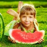Χαριτωμένο μικρό κορίτσι που τρώει το καρπούζι και που βρίσκεται στην πράσινη χλόη στοκ εικόνα