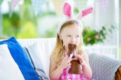 Χαριτωμένο μικρό κορίτσι που φορά τα αυτιά λαγουδάκι που τρώνε το κουνέλι Πάσχας σοκολάτας Στοκ εικόνα με δικαίωμα ελεύθερης χρήσης