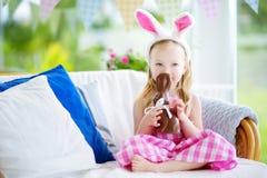 Χαριτωμένο μικρό κορίτσι που φορά τα αυτιά λαγουδάκι που τρώνε το κουνέλι Πάσχας σοκολάτας Στοκ Εικόνες