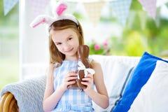 Χαριτωμένο μικρό κορίτσι που φορά τα αυτιά λαγουδάκι που τρώνε το κουνέλι Πάσχας σοκολάτας Στοκ φωτογραφίες με δικαίωμα ελεύθερης χρήσης