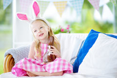 Χαριτωμένο μικρό κορίτσι που φορά τα αυτιά λαγουδάκι που τρώνε το κουνέλι Πάσχας σοκολάτας Στοκ Εικόνα