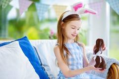 Χαριτωμένο μικρό κορίτσι που φορά τα αυτιά λαγουδάκι που τρώνε το κουνέλι Πάσχας σοκολάτας Στοκ φωτογραφία με δικαίωμα ελεύθερης χρήσης