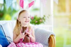 Χαριτωμένο μικρό κορίτσι που φορά τα αυτιά λαγουδάκι που τρώνε το κουνέλι Πάσχας σοκολάτας Στοκ Φωτογραφία