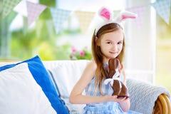 Χαριτωμένο μικρό κορίτσι που φορά τα αυτιά λαγουδάκι που τρώνε το κουνέλι Πάσχας σοκολάτας Στοκ Φωτογραφίες