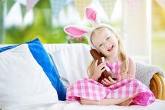 Χαριτωμένο μικρό κορίτσι που φορά τα αυτιά λαγουδάκι που τρώνε το κουνέλι Πάσχας σοκολάτας Στοκ εικόνες με δικαίωμα ελεύθερης χρήσης