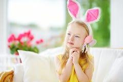 Χαριτωμένο μικρό κορίτσι που φορά τα αυτιά λαγουδάκι που παίζουν το κυνήγι αυγών σε Πάσχα Στοκ Φωτογραφία