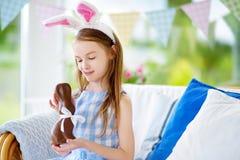 Χαριτωμένο μικρό κορίτσι που φορά τα αυτιά λαγουδάκι που τρώνε το κουνέλι Πάσχας σοκολάτας Παίζοντας κυνήγι αυγών παιδιών σε Πάσχ Στοκ φωτογραφία με δικαίωμα ελεύθερης χρήσης