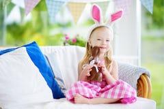 Χαριτωμένο μικρό κορίτσι που φορά τα αυτιά λαγουδάκι που τρώνε το κουνέλι Πάσχας σοκολάτας Παίζοντας κυνήγι αυγών παιδιών σε Πάσχ Στοκ εικόνες με δικαίωμα ελεύθερης χρήσης