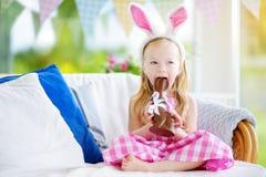Χαριτωμένο μικρό κορίτσι που φορά τα αυτιά λαγουδάκι που τρώνε το κουνέλι Πάσχας σοκολάτας Παίζοντας κυνήγι αυγών παιδιών σε Πάσχ Στοκ Εικόνες