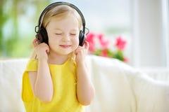 Χαριτωμένο μικρό κορίτσι που φορά τα τεράστια ασύρματα ακουστικά Όμορφο παιδί που ακούει τη μουσική Μαθήτρια που έχει τη διασκέδα Στοκ Φωτογραφίες
