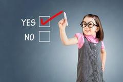 Χαριτωμένο μικρό κορίτσι που φορά το επιχειρησιακό φόρεμα και που σύρει ΝΑΙ σε ένα whiteboard πρόσκληση συγχαρητηρίων καρτών ανασ Στοκ Εικόνες