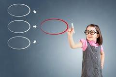Χαριτωμένο μικρό κορίτσι που φορά το επιχειρησιακό φόρεμα και που επισύρει την προσοχή το διάγραμμα στο whiteboard πρόσκληση συγχ Στοκ Εικόνες