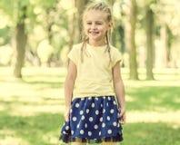 Χαριτωμένο μικρό κορίτσι που χαμογελά στο πάρκο πρωινού στοκ εικόνα με δικαίωμα ελεύθερης χρήσης