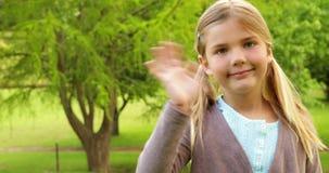Χαριτωμένο μικρό κορίτσι που χαμογελά και που κυματίζει απόθεμα βίντεο