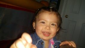 Χαριτωμένο μικρό κορίτσι που χαμογελά με τα μεγάλα λακκάκια και briwn τα μάτια της για τη κάμερα Στοκ Εικόνα