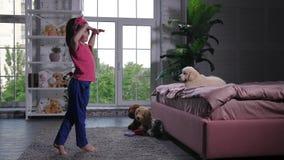 Χαριτωμένο μικρό κορίτσι που χορεύει για το κουτάβι που βρίσκεται στο κρεβάτι φιλμ μικρού μήκους