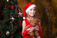 Χαριτωμένο μικρό κορίτσι σε ένα κόκκινο φόρεμα κοντά σε ένα χριστουγεννιάτικο δέντρο Στοκ φωτογραφία με δικαίωμα ελεύθερης χρήσης