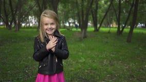 Χαριτωμένο μικρό κορίτσι σε ένα σακάκι δέρματος που χτυπά σε ένα πάρκο απόθεμα βίντεο