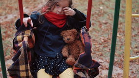 Χαριτωμένο μικρό κορίτσι σε μια παλαιά ταλάντευση με τη teddy αρκούδα της στο πάρκο φθινοπώρου 4k απόθεμα βίντεο