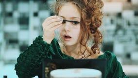 Χαριτωμένο μικρό κορίτσι σε μια πράσινη συνεδρίαση χρώματος φορεμάτων eyelashes κοντά σε έναν καθρέφτη απόθεμα βίντεο