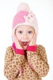 Χαριτωμένο μικρό κορίτσι στα κόκκινα χέρια εκμετάλλευσης καπέλων για να αντιμετωπίσει στην έκπληξη στοκ φωτογραφία με δικαίωμα ελεύθερης χρήσης