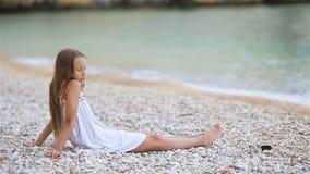 Χαριτωμένο μικρό κορίτσι στην παραλία κατά τη διάρκεια των θερινών διακοπών απόθεμα βίντεο