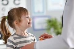 Χαριτωμένο μικρό κορίτσι στην υποδοχή γιατρών που παίρνει τη συνταγή φαρμάκων στοκ εικόνες