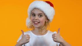 Χαριτωμένο μικρό κορίτσι στο καπέλο Άγιου Βασίλη που παρουσιάζει αντίχειρες και που χαμογελά στη κάμερα απόθεμα βίντεο