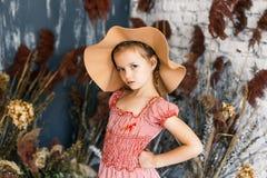 Χαριτωμένο μικρό κορίτσι στο μοντέρνο καπέλο με τα peonies στο στούντιο στοκ φωτογραφία με δικαίωμα ελεύθερης χρήσης