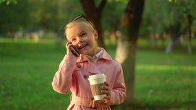 Χαριτωμένο μικρό κορίτσι στο ρόδινο χαμόγελο και την ομιλία στο τηλέφωνο στο πάρκο φιλμ μικρού μήκους