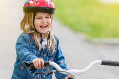 Χαριτωμένο μικρό κορίτσι στο σακάκι κρανών και τζιν σε ένα ποδήλατο Στοκ φωτογραφία με δικαίωμα ελεύθερης χρήσης