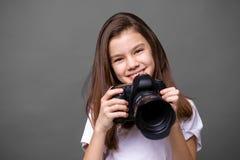 Χαριτωμένο μικρό κορίτσι brunette που κρατά μια κάμερα φωτογραφιών Στοκ φωτογραφία με δικαίωμα ελεύθερης χρήσης