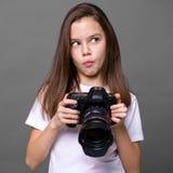 Χαριτωμένο μικρό κορίτσι brunette που κρατά μια κάμερα φωτογραφιών Στοκ Φωτογραφίες