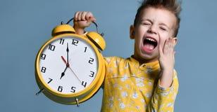 Χαριτωμένο μικρό παιδί με το ξυπνητήρι, που απομονώνεται στο μπλε Αστείο παιδί που δείχνει στο ξυπνητήρι σε 7 η ώρα στο πρωί στοκ εικόνα