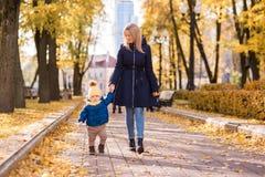 Χαριτωμένο μικρό παιδί με το φθινόπωρο μητέρων της στοκ φωτογραφίες
