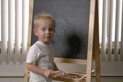 Χαριτωμένο μικρό παιδί μικρών παιδιών, δύο χρονών Στρέθιμο της προσοχής στο chalkbo στοκ εικόνα με δικαίωμα ελεύθερης χρήσης