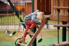 Χαριτωμένο μικρό παιδί που έχει τη διασκέδαση στην υπαίθρια παιδική χαρά Στοκ Εικόνα