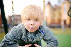 Χαριτωμένο μικρό παιδί που έχει τη διασκέδαση στην υπαίθρια παιδική χαρά Στοκ Εικόνες