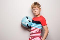 Χαριτωμένο μικρό παιδί που στέκεται με τη σφαίρα ποδοσφαίρου και που εξετάζει τη κάμερα r Πορτρέτο στούντιο στοκ εικόνες