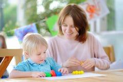 Χαριτωμένο μικρό παιδί που σύρει και που χρωματίζει με τις ζωηρόχρωμες μάνδρες δεικτών στον παιδικό σταθμό Στοκ Εικόνα